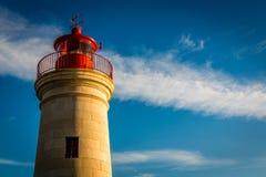 Leuchtturmsonnenuntergang mit blauem Himmel und Wolken Lizenzfreies Stockbild