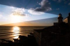 Leuchtturmsonnenunterganglichtstrahlen Lizenzfreie Stockfotos