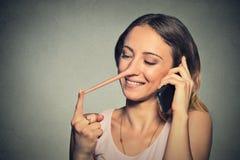 Leugenaarconcept Gelukkige vrouw met lange neus die op mobiele telefoon spreken Stock Foto's
