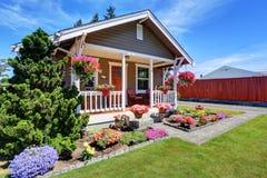 Leuk Amerikaans huis buiten met behandelde portiek en bloempotten stock foto