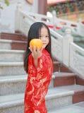 Leuk Aziatisch jong geitjemeisje in Traditionele Chinese kleding met het houden van heilige Sinaasappel bij Chinese tempel in Ban stock afbeeldingen
