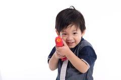 Leuk Aziatisch jongen het spelen stuk speelgoed kanon Stock Afbeeldingen