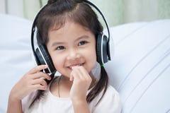 Leuk Aziatisch kindmeisje die in hoofdtelefoons de muziek luisteren royalty-vrije stock afbeelding