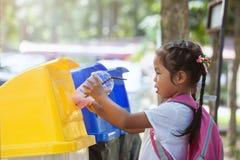 Leuk Aziatisch kindmeisje die plastic glas in het recycling van afval werpen royalty-vrije stock foto