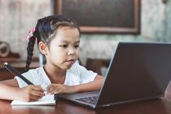 Leuk Aziatisch kindmeisje gebruikend laptop en schrijvend op haar notitieboekje stock foto's