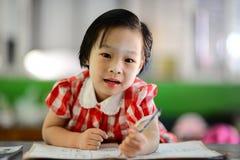 Leuk Aziatisch meisje die haar thuiswerk doen royalty-vrije stock afbeelding