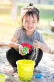 Leuk Aziatisch meisje het spelen zand met zonlicht stock foto