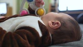 Leuk babyjongen het spelen stuk speelgoed Het leuke kind spelen met rammelaar op bed stock video