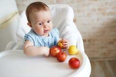 Leuk babymeisje die appel in de keuken eten Weinig jong geitje proevende vaste lichamen thuis De baby leidde het spenen De ruimte royalty-vrije stock foto