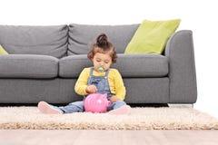Leuk babymeisje die een muntstuk zetten in een piggybank Royalty-vrije Stock Foto