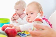 Leuk babymeisje die gezond stevig voedsel in een modern opvangcentrum eten stock fotografie