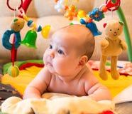 Leuk babymeisje die op de achtergrond liggen Stock Afbeelding