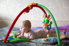 Leuk babymeisje die op de achtergrond van stuk speelgoed liggen Stock Afbeelding