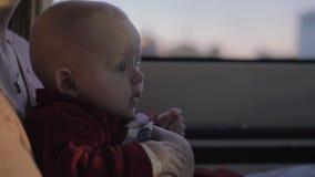 Leuk babymeisje die op moederoverlapping in auto aan de weg met nieuwsgierigheid kijken stock video