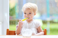 Leuk babymeisje die yoghurt van lepel eten Stock Afbeelding