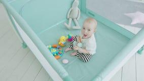 Leuk babymeisje het spelen speelgoed in box thuis stock video