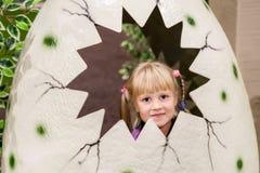 Leuk babymeisje in kunstmatig gebarsten dinosaurusei weinig Jong geitje die en pret glimlachen hebben bij binnenspeelplaats stock foto