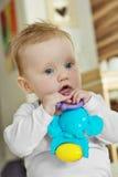 Leuk babymeisje met een stuk speelgoed Stock Afbeeldingen