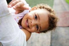 Leuk babymeisje op haar moeder`s wapens Stock Fotografie