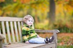 Leuk babymeisje op houten bank in de herfstpark Royalty-vrije Stock Foto