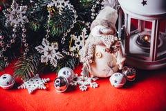 Leuk bevindt weinig aanbiddelijke sneeuwman zich dichtbij de witte feelantaarn en de verfraaide sparrentak achter het Stock Afbeelding