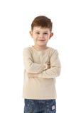 Leuk bewapent weinig jongen die het gekruiste glimlachen bevindt zich Stock Fotografie
