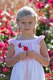 Leuk blond meisje dat rode bloem houdt Stock Foto