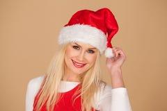 Leuk blond meisje in een feestelijke rode Kerstmanhoed Royalty-vrije Stock Foto