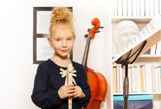 Leuk blond meisje met fluit die zich dichtbij cello bevinden Stock Fotografie