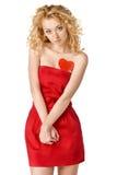 Leuk blond meisje in rode kleding met een hart Stock Fotografie