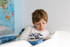 Leuk blond weinig jong geitjejongen die in pyjama's boek in zijn slaapkamer lezen stock foto's