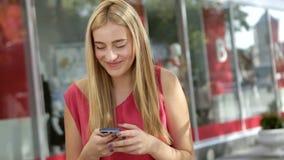 Leuk blonde die met haar vrienden babbelen die telefoon op de straat met behulp van stock video