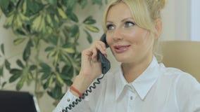 Leuk blonde die op de telefoon in bureau spreken stock video