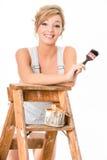 Leuk blondemeisje, in overall, die op oude ladder rusten royalty-vrije stock foto