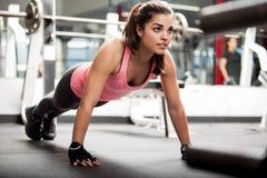 Leuk brunette die bij een gymnastiek uitwerken stock foto