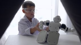 Leuk de robotstuk speelgoed van jong geitjereparaties met Kunstmatige intelligentie in ruimte stock footage