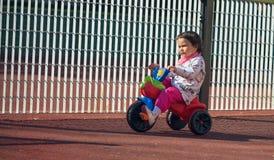 Leuk drie-jaar-oud weinig kind die een 3 wielfiets in speelplaats berijden Royalty-vrije Stock Afbeelding