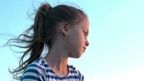 Leuk dromerig meisje in gestreept overhemd op hemelachtergrond met evoluerend haar bij zonsondergang stock footage