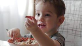 Leuk eet weinig baby alleen havermoutpap met een lepel van een plaat, het concept het gezonde eten stock footage