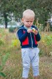 Leuk eet weinig jongen rode sappige appel in een tuin in het dorp stock afbeelding