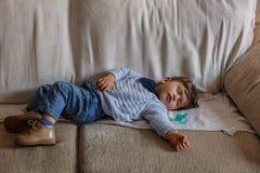 Leuk en weinig jongen gekleed in blauwe en bruine schoenen, slaapt vreedzaam op bank in de woonkamer van zijn huis royalty-vrije stock afbeeldingen