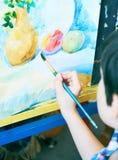 Leuk, ernstig en geconcentreerd, zeven jaar oude jongens die in blauw overhemd op canvas trekken die zich op de schildersezel bev stock foto