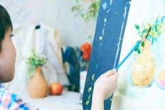 Leuk, ernstig en geconcentreerd, zeven jaar oude jongens die in blauw overhemd op canvas trekken die zich op de schildersezel bev stock afbeeldingen