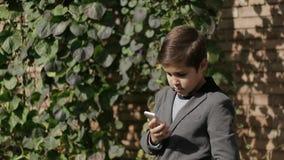 Leuk gebruikt weinig Jongen in jasje zijn telefoon Achtergrond van klimopmuur stock video
