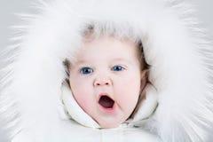 Leuk geeuwend babymeisje die reusachtige witte bonthoed dragen Stock Afbeeldingen