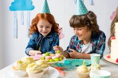 leuk gelukkig jongen en meisje die in partijkegels snoepjes eten bij verjaardag Stock Fotografie