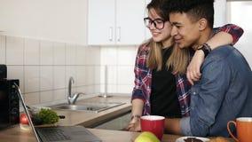 Leuk gelukkig paar die bij iemand in hun laptop golven, het video babbelen terwijl thuis geknuffel in hun keuken living stock video