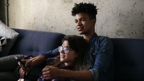 Leuk gelukkig paar van jonge hipsters die op de laag liggen, makend dwaze gezichten, die een perfect TV-kanaal proberen te vinden stock video