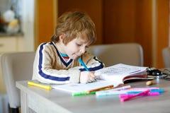 Leuk gelukkig schoolkind die thuis thuiswerk maken stock fotografie