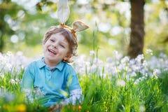 Leuk gelukkig weinig jongen die Paashaasoren dragen bij groene de lente Stock Foto